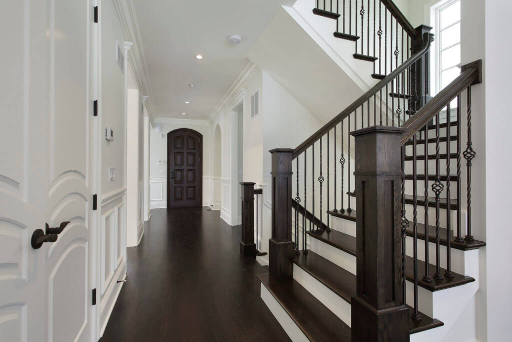 Hallway of a home with white walls and a dark wood staircase and front door.