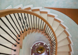 looking down on a spiral flight of stairs with a light wood banister and wood treads with a carpet runner