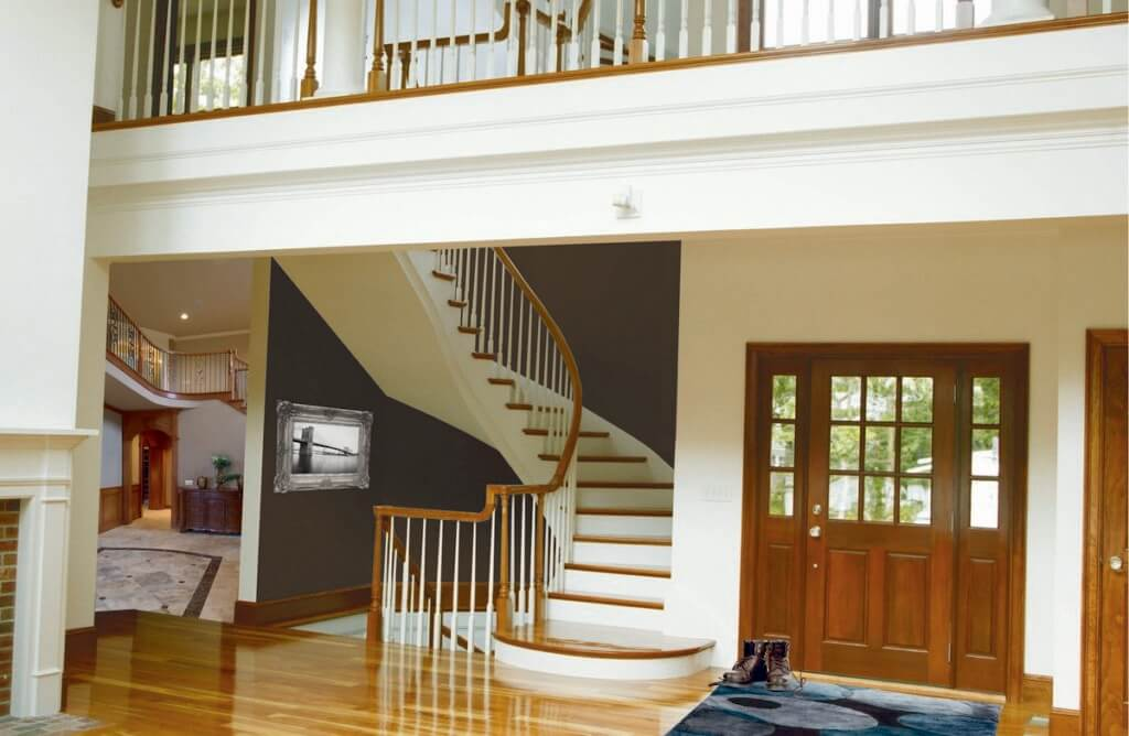 Foyer with a door to the right of a curved maple and poplar staircase